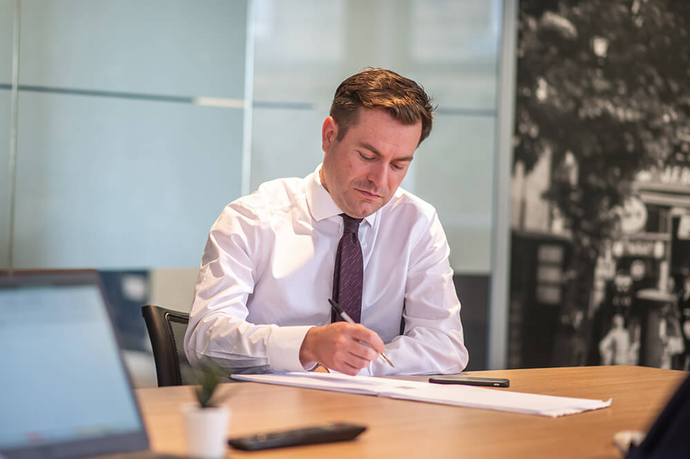 man writing in boardroom