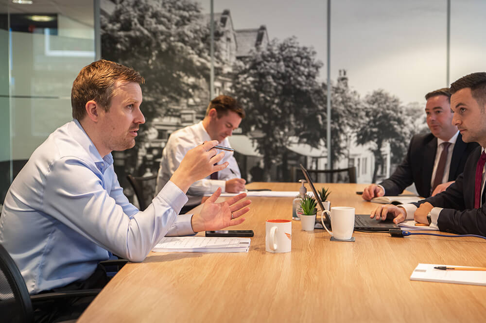 four men at a boardroom table